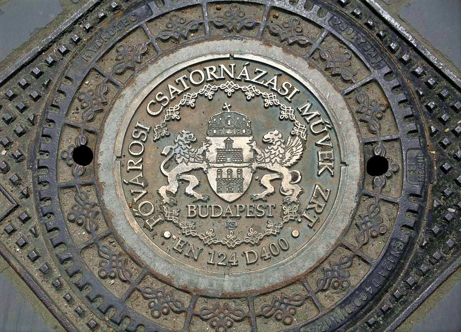 A circular sewer lid decorated with intricate patterns and the coat of arms of Budapest at the center