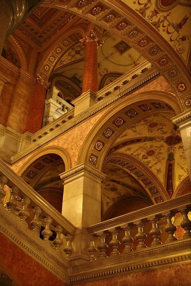 An opulent multilevel hall of archways and intricately decorated ceilings