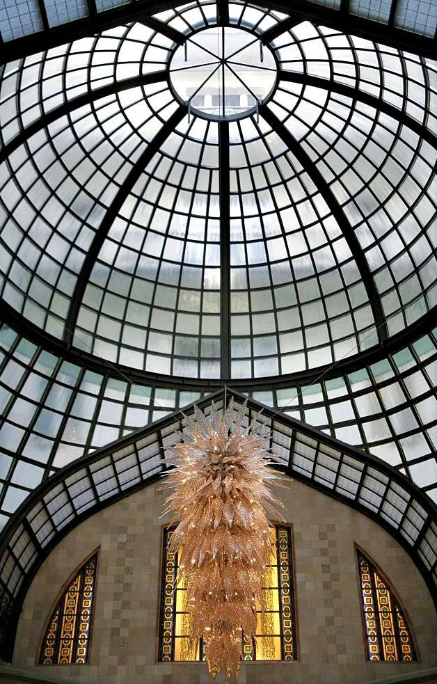 A glass dome from which hangs an intricate glass chandelier