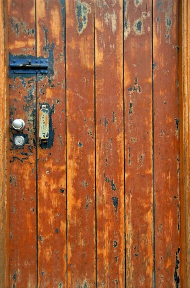 An old wooden door with a worn, textured surface. Its colour is a rich orange-brown of varying tones.