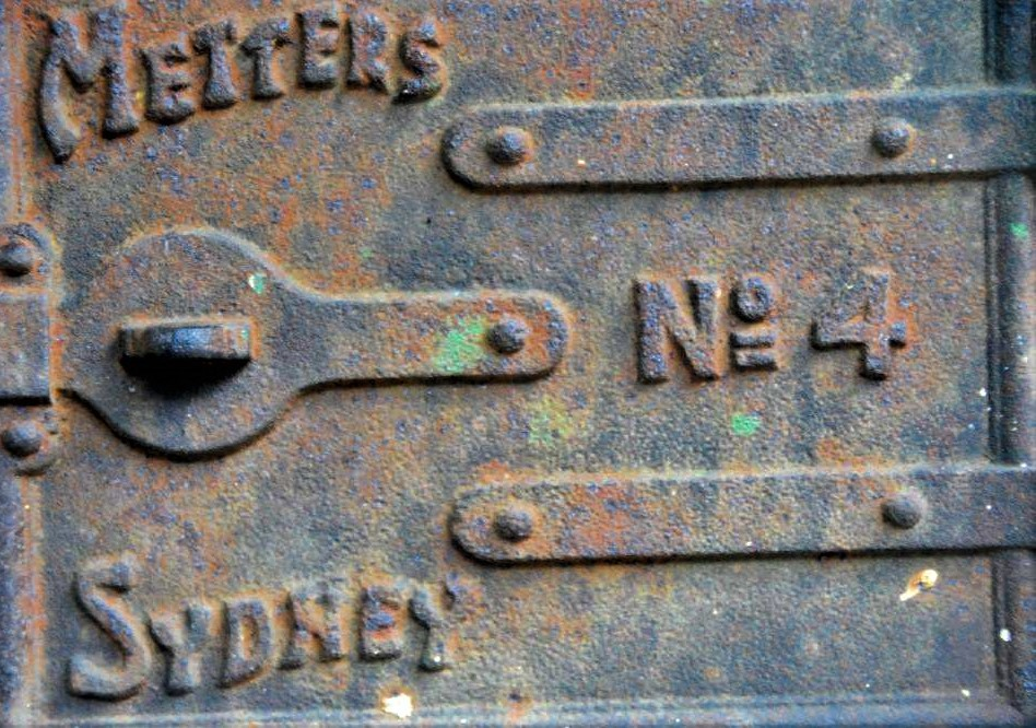 The rusted metal door of an antique safe, featuring words that read 'Metters No. 4, Sydney'.