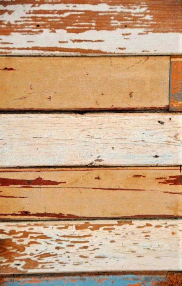 A close-up photo of weathered wooden planks with a layered texture and varying shades of brown and tan.