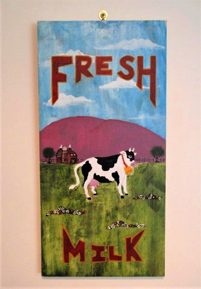 A hand-painted sign that reads 'fresh milk' and features a black and white cow grazing in a green pasture