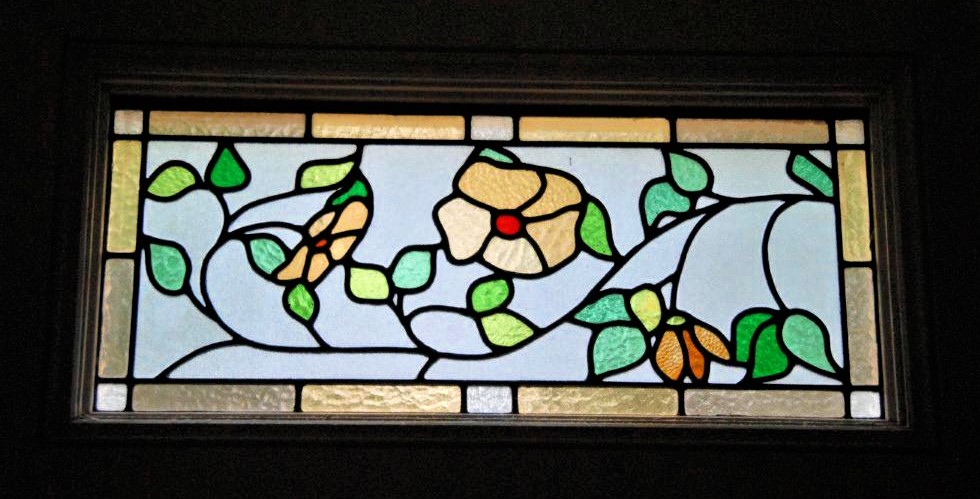 A rectangular stained glass window featuring yellow flowers and green leaves