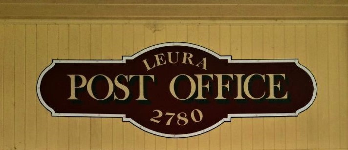 A dark-brown antique sign that reads 'Leura Post Office 2780'. It hangs on a pale mustard-yellow wall.